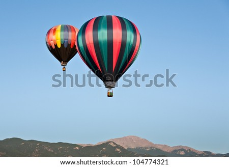 A hot air balloon ascends in the skies above Pikes Peak during the 2011 Colorado Balloon Classic