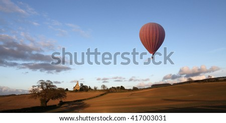A hot air balloon drifts slowly over the North Yorkshire countryside in the late afternoon sun - England - stock photo