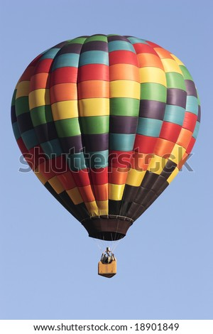 A hot air balloon floats on a beautiful day.