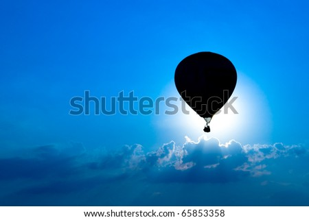 A hot air balloon is silhouetted against a bright blue sky as it eclipses the sun. - stock photo