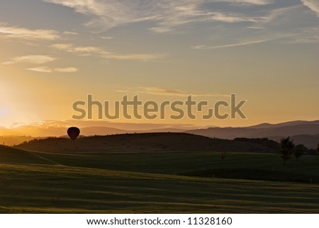 A hot air balloon landing on a golf course at sunset - stock photo