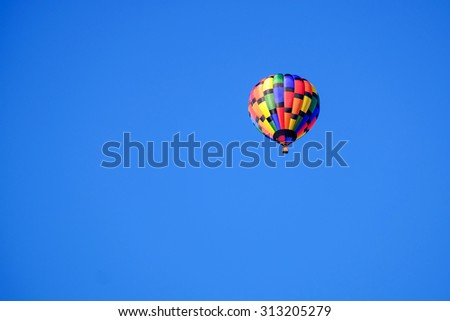 A hot air balloon with a rainbow livery floating in the sky.