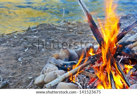 A hot campfire burns next to a river. - stock photo