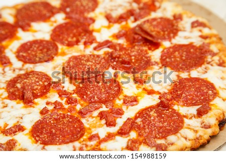 A hot, cheesy, pepperoni pizza with grease and melted cheese - stock photo