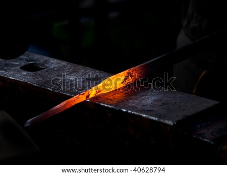 A hot metal rod being hammered on an anvil by a Blacksmith. - stock photo