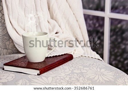 A hot relaxing cup of coffee or cocoa with a book sitting on a comfortable chair with blanket. Extreme shallow depth of field.  - stock photo