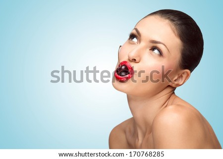 A hot sexy chic with gorgeous body holding a tasty cherry with juicy lips. - stock photo