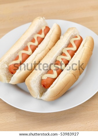 A hotdog with mustard sauce on a kitchen bench - stock photo