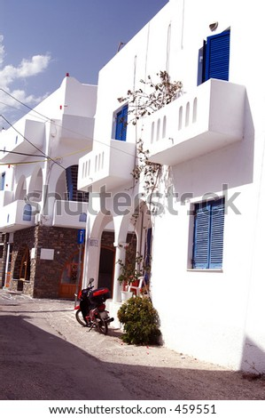 a hotel in the greek islands with a motorbike parked outside - stock photo