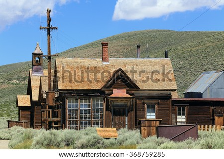 A house and a church are among the buildings still standing at Bodie Ghost Town in California. - stock photo