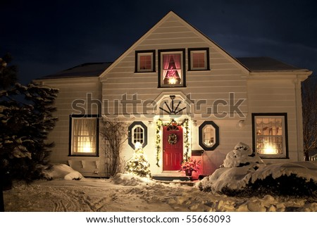 A house decorated with a wreath, garland and Christmas lights an a clear winter night. - stock photo