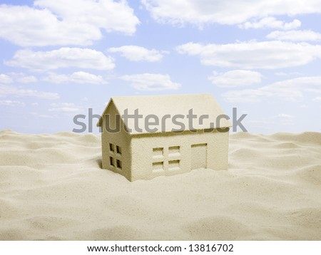 a house from sand and a cloudy sky on the beach - stock photo