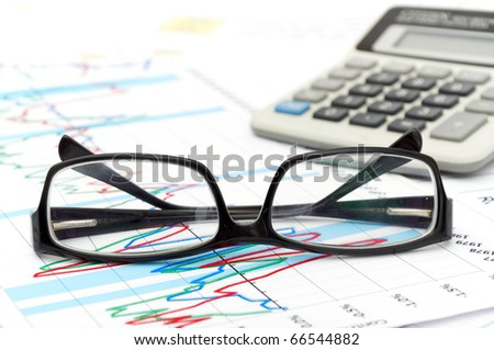 a house hold budget with glasses and calculator - stock photo