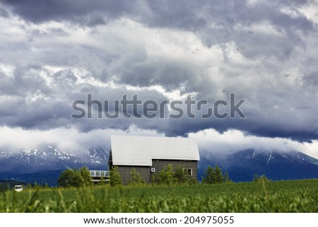A house in grass field with mountain background, Hokkaido, Japan - stock photo