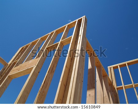 A house is being built on a construction site.  The walls have been put up and the frame can be seen.  Horizontally framed shot.