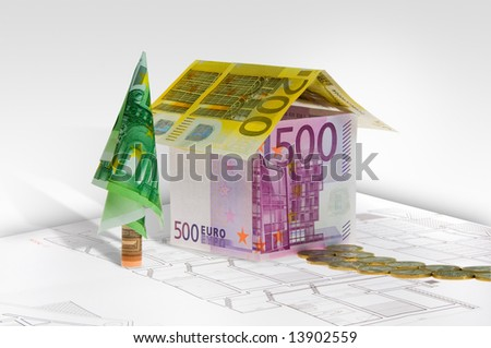 A house made of euro banknotes on plan with path of coin. Conceptual image. - stock photo