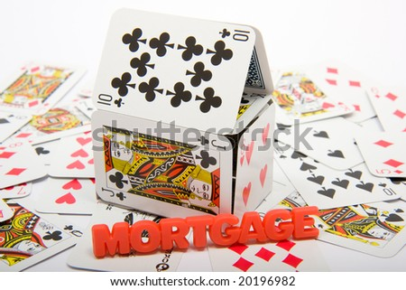 A house made of playing cards on top of a collapsed set of cards - stock photo