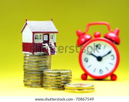 A house placed on a stack of gold coins with a red alarm clock behind, asking the question is it time to buy that dream house?