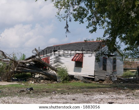 a house rests on a tree that it uprooted when carried by the floodwaters from the Industrial Canal levee breach - photo taken a year after Hurricane Katrina struck - stock photo