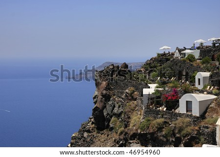 A house set on a hill overlooking the sea. Viewpoint at Santorini. - stock photo