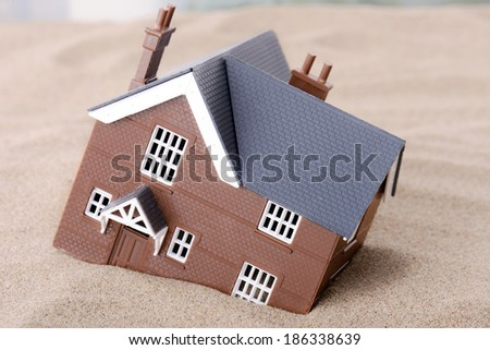 A house sinking in sand, concept for housing problems - stock photo