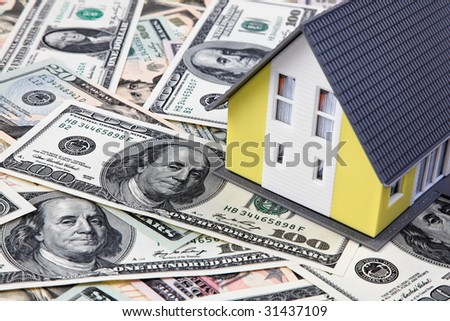 A house stands on many dollars banknotes