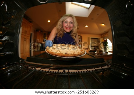 a house wife bakes a apple pie for her hungry family for desert. apple pies are as American as well Apple Pie. Shot from inside the oven for a unique view not often seen - stock photo