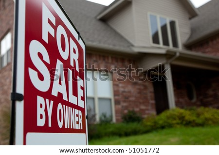 A house with a red for sale sign in the yard - stock photo