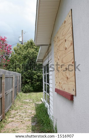 A house with plywood on the window in preparation for a hurricane.  Storm clouds overhead.  Vertical view. - stock photo