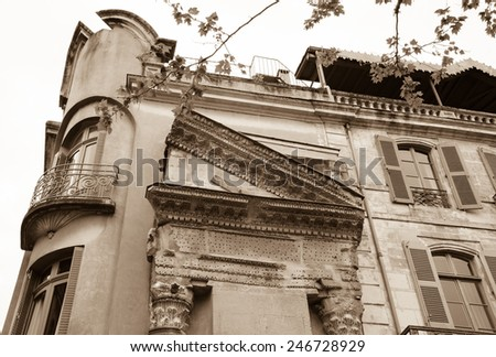 A house with Roman portico and columns in Arles (Provence, France). Aged photo. Sepia. - stock photo