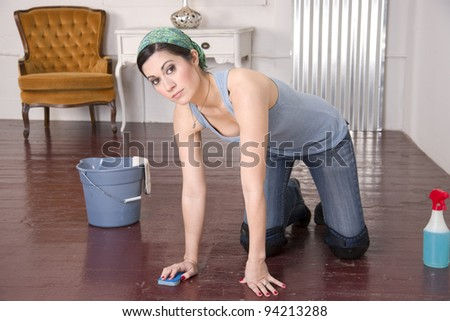 A housekeeper cleaning wood floor on her knees looking at the Camera