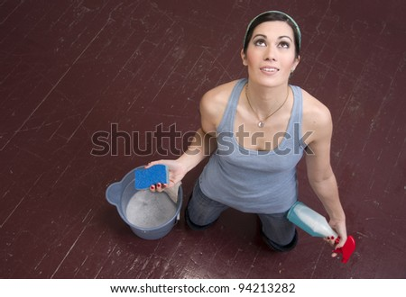 A housekeeper on her knees looking up to the sky tired cleaning lady