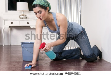 A housekeeper on her knees washing the floor the old fashioned way
