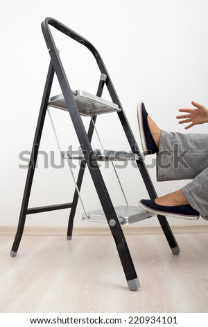 A housewife falling from a ladder showing importance of  home safety and health. - stock photo