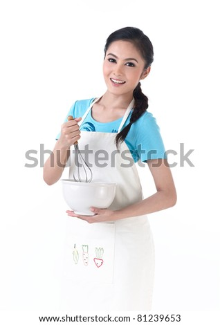 A housewife holding a bowl and stirring eggs - stock photo