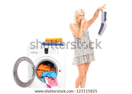 A housewife holding a male sock and her nose next to a washing machine isolated on white - stock photo