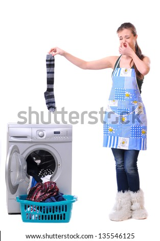 A housewife holding a male sock and her nose next to a washing machine isolated on white