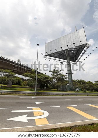 A huge blank unipole advertisement billboard along a motor highway with traffic arrow signage. - stock photo