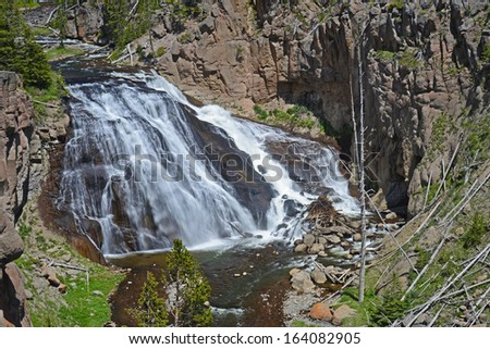 A huge cascading waterfall dominates the scene. - stock photo