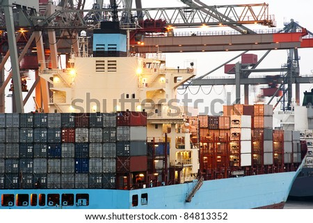 A huge container ship being unloaded at dawn in an industrial harbor by overhead cranes - stock photo