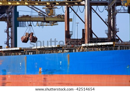 A huge crane unloading ore from a bulk carrier - stock photo