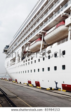 A huge cruise liner boat with port hole windows on its hull docked at a jetty. - stock photo