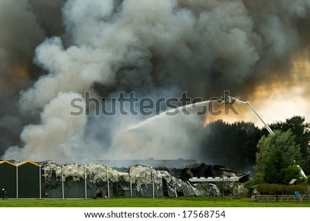 a huge fire with firefighters in action - stock photo