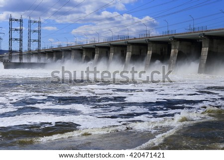 A huge force of water and the nature at the dam Reset water on the river at the dam in the spring, at the top of the bridge - stock photo