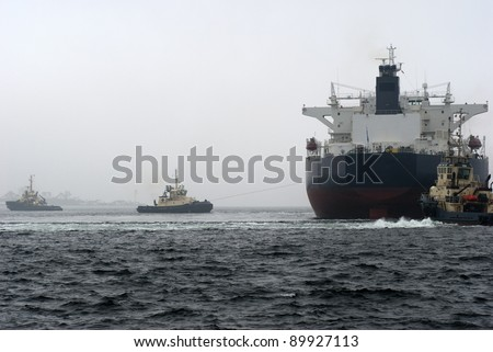 A huge Greek oil tanker and three tugboats at work