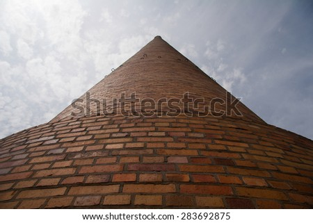 a huge industrial chimney from the frog perspective - stock photo