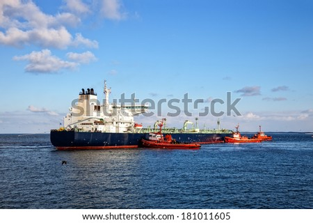 A huge oil tanker and three tugboats at work.  - stock photo