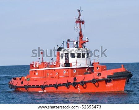 A huge orange tugboat in a harbor;