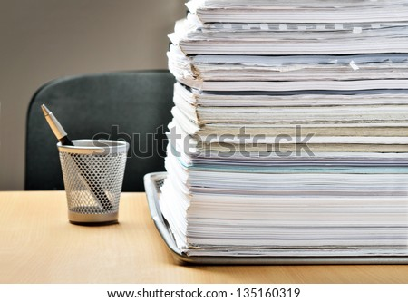 A huge pile of paperwork on a desk - stock photo
