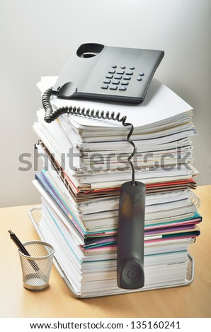 A huge pile of paperwork on a desk and a phone above it